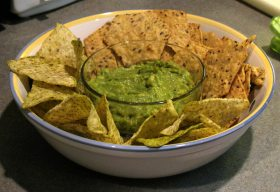 Bowl of avocado dip surrounded by chips.